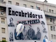 Bandera sobre papel prensa y dueños clarin con la fraseencubridores